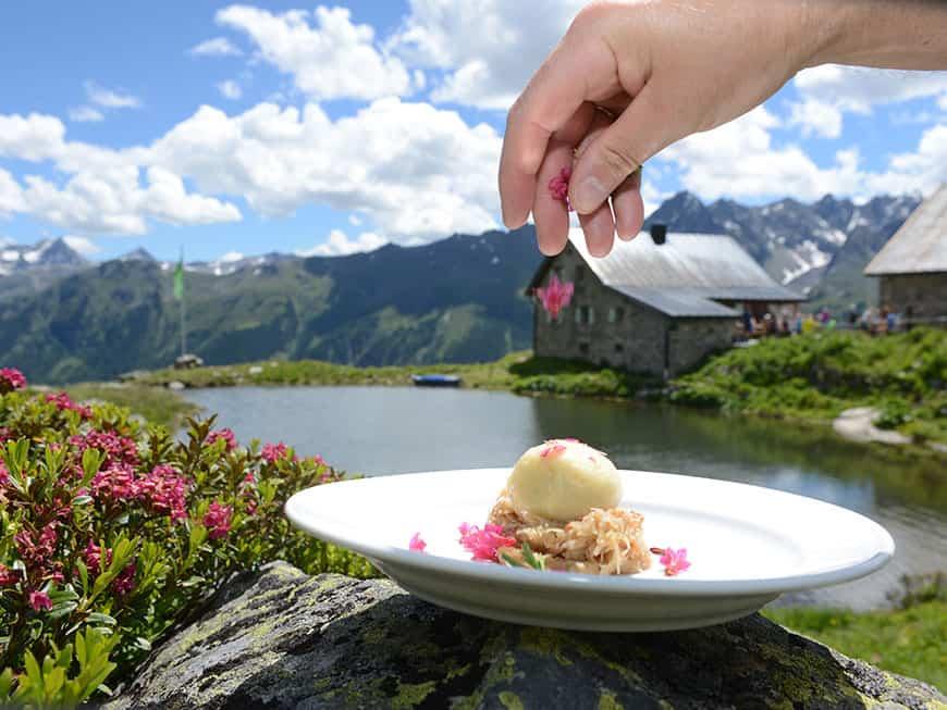 Knödel auf Sauerkraut mit Wildblumen dekoriert vor einer Berglandschaft
