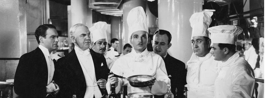 Ein Koch mit Pfanne in den Händen umrundet von seinen Kollegen