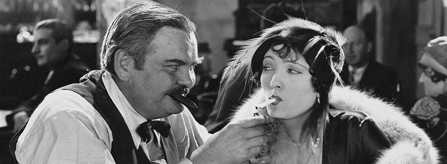 ein Mann bietet einer Dame mit Zigarette im Mund Feuer an