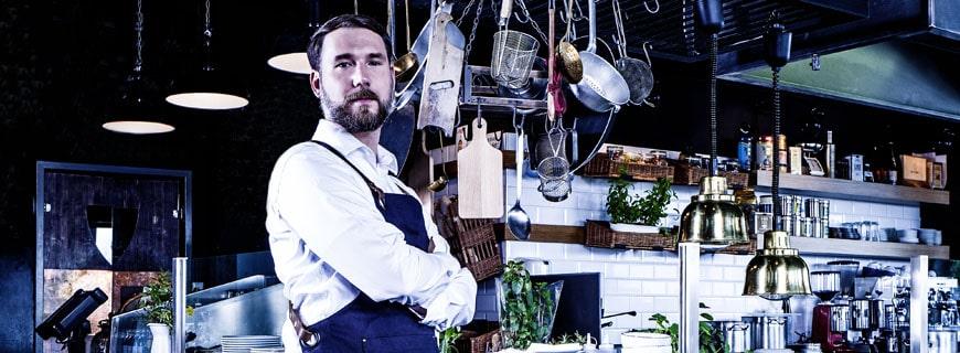 Dennis Maier steht in einer blauen Küche
