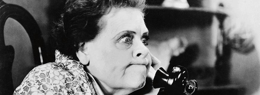 Eine frau greift verärgert zum Telefonhörer
