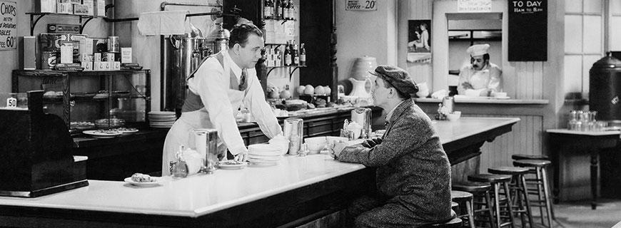 szene aus stummfilm: mann sitzt am barhocker und bestellt beim barkeeper