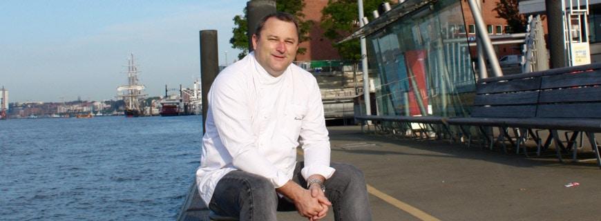 Foto von Martin Kirchgasser, neuer Küchenchef im Westin Hamburg in der Elbphilharmonie, sitzt auf einem Pfeiler am Hamburger Hafen.
