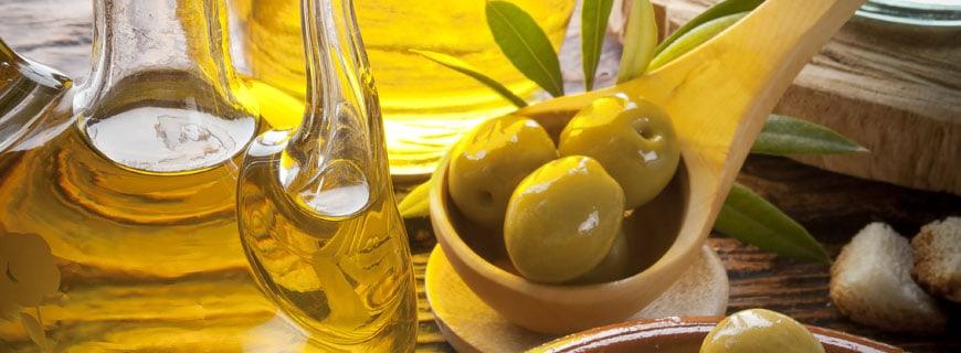 Olivenöl und Oliven im Holzlöffel