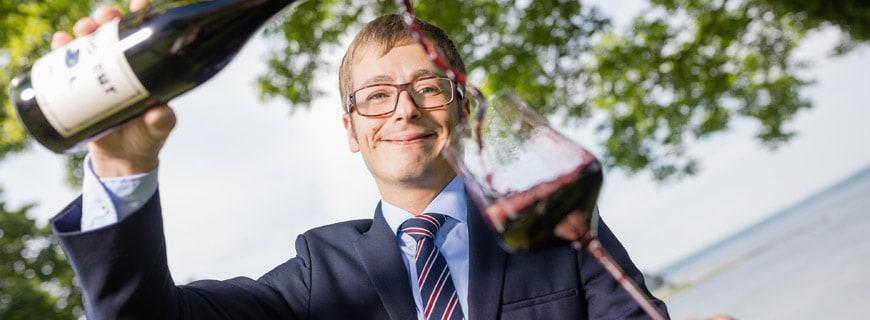 Tim Blaszyk ist neuer Restaurantleiter und Sommelier im Vitalhotel Alter Meierhof und schüttet Rotwein in ein Glas