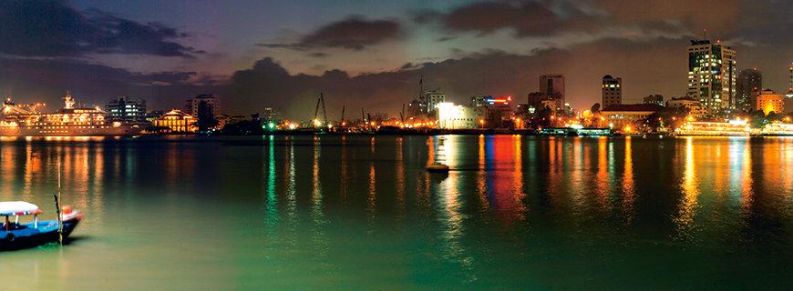 ein Hafen mit kleinen Booten, im Hintergrund das Leuchten der Stadt