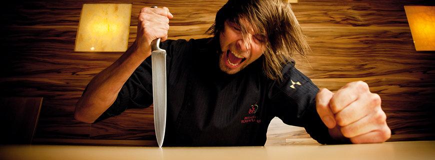 Christian Winkler mit einem Messer dass er in den Tisch rammt