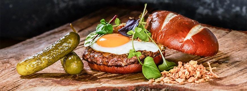 Burger mit Laugenbun, Gewürzgurke, Spiegelei und Fleischpatty im C's Authentic Food in Koblenz