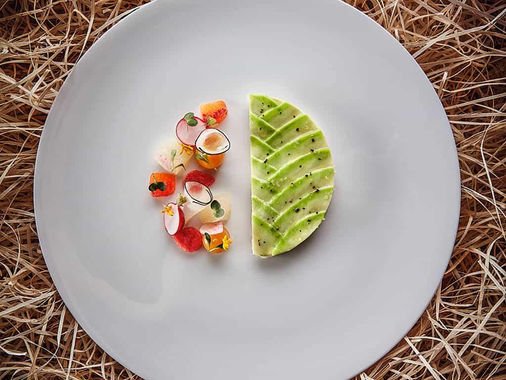 Weißer Teller mit kreisförmig angerichteter Meeresspinne | Avocado | Zitrusfrüchte | Koriander | Radieschen