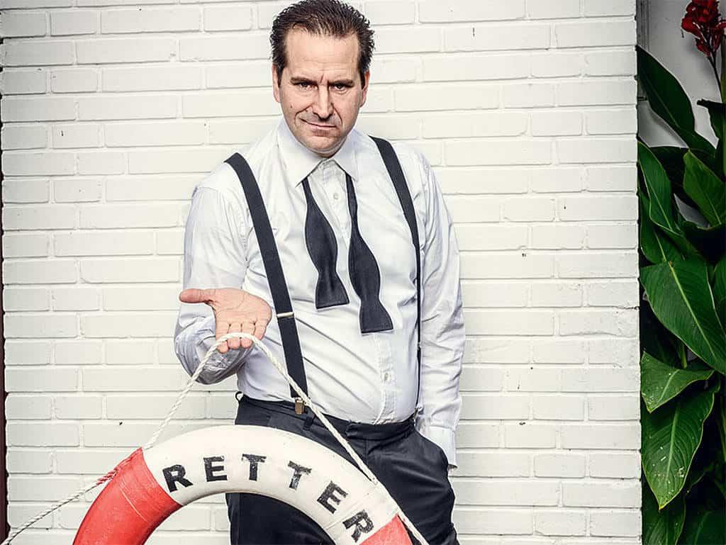 Gerhard Retter hält einen Rettungsring in der Hand, mit offener Fliege und Hosenträger