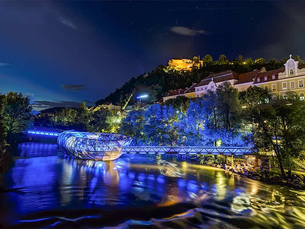 Graz bei Nacht: Blick auf die Murinsel, im Hintergrund strahlt der Schloßberg hell erleuchtet