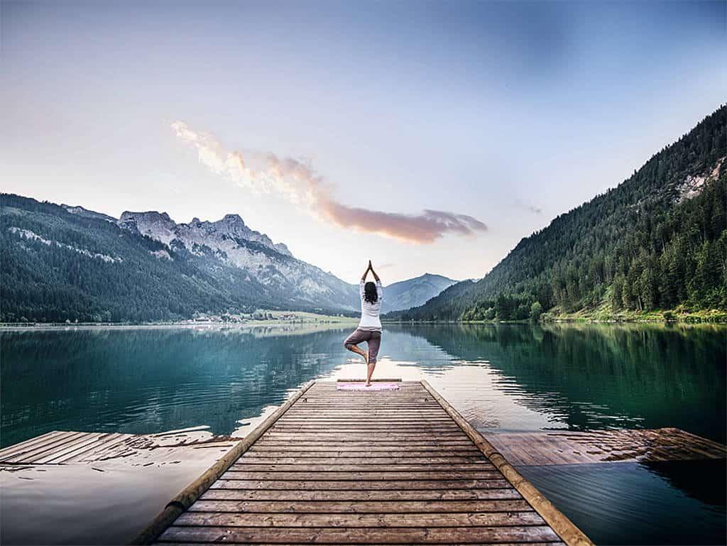 Eine Frau beim Yoga am Steeg eines Bergsees