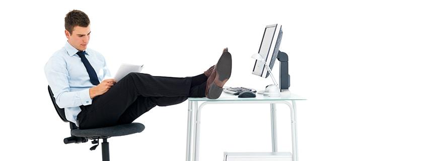 ein Herr im Büro, die Beine verschränkt auf den Tisch gelegt