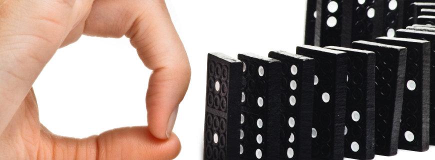 eine Hand dabei eine Dominoreihe umzustossen
