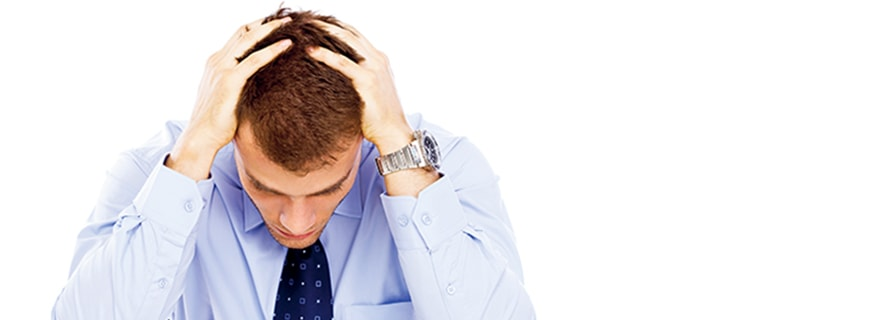 ein Mann den Kopf in die Hände stützend, sichtilich verzweifelt