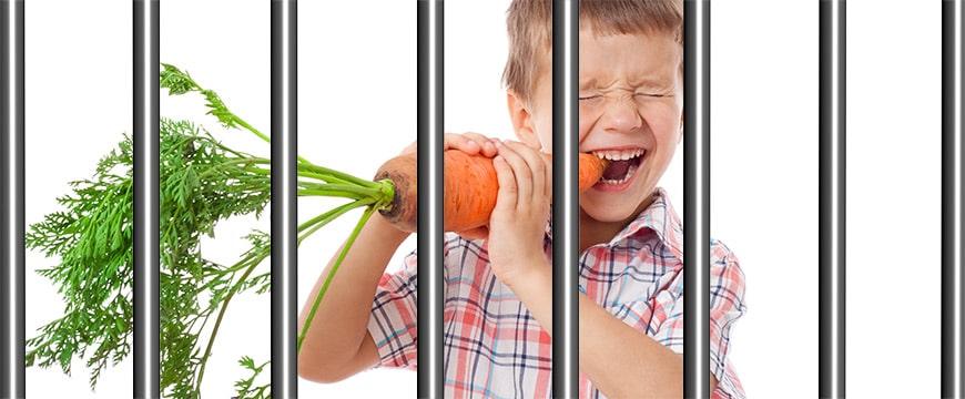 Kind mit Karotte hinter Gittern