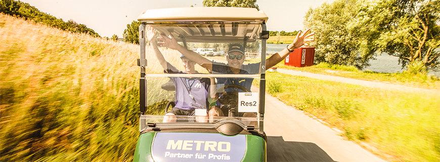 Metro-Golfcar mit zwei Personen aus dem Team