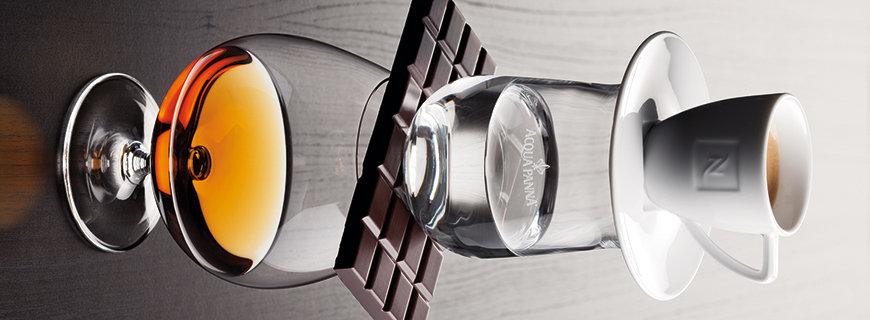 Whisky, Schokolade, Wasser und Kaffee zu einem Turm gestapelt
