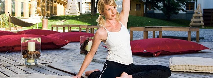 eine Frau betreibt Yoga im Garten des Hotels