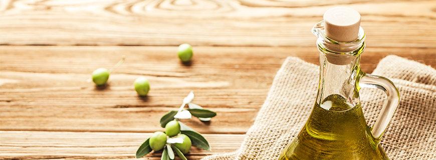 Olivenölflasche auf einem Tisch, mit einem Olivenölzweig daneben