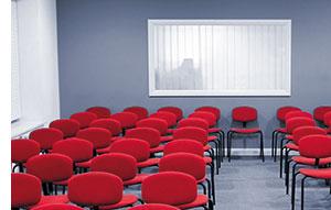 ein Seminarraum mit roten Stoffstühlen
