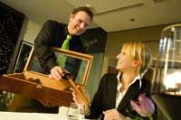 Ein stehender Herr bietet aus einer Zigarrenbox einer sitzenden Dame eine Zigarre an