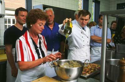eine Gruppe besucht einen Kochkurs, der Kochlehrer gießt Olivenöl in die Teigmasse einer Dame