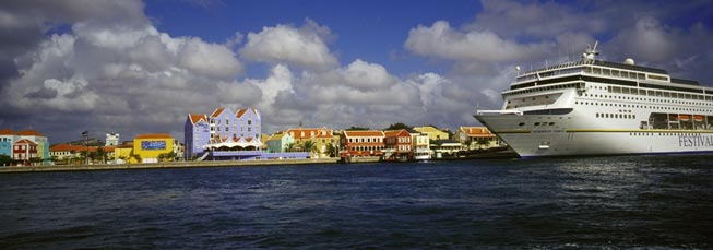 ein Passagierschiff fährt an der Küste eines kleinen idyllischen Ortes vorbei