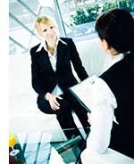 eine Frau sitzt bei ihrem Bewerbungsgespraech