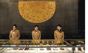 drei Mitarbeiterinnen eines Hotels in Japan hinter einer Theke unter der sich japanische Köstlichkeiten verbergen
