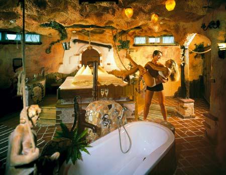 ein Mann trägt eine Frau auf Händen in einer romantischen Badlandschaft