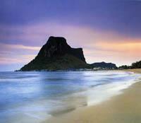 ein Sandstrand und türkisblaues Meer, ein Berg und ein rosa-blauer Himmel in der Dämmerung