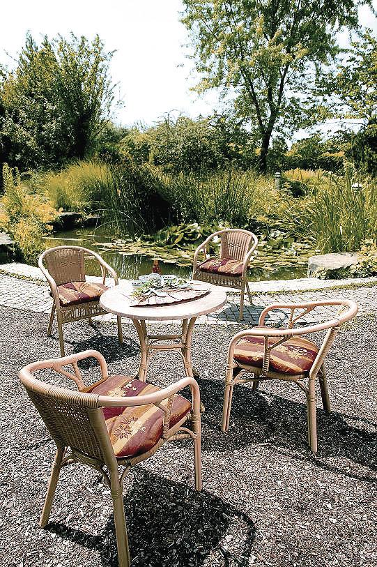 Ein Bistrotisch mit Sesseln aus Rattan Textur neben einem Teich in der Sonne