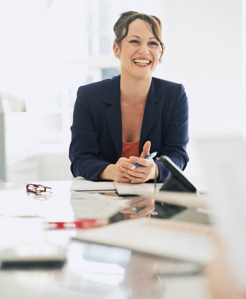 eine Geschäftsfrau sitzt im Blazer an einem Schreibtisch und lächelt