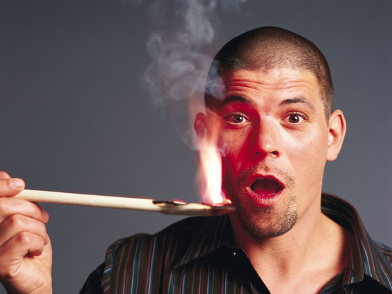 der Erfolgreiche TV-Koch Tim Mälzer mit einem brennenden Stab, sein Mund zu einem O geformt vor staunen