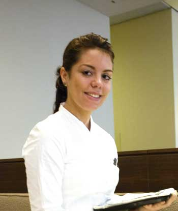 eine junge Dame im weißen Hemd lächelt in die Kamera