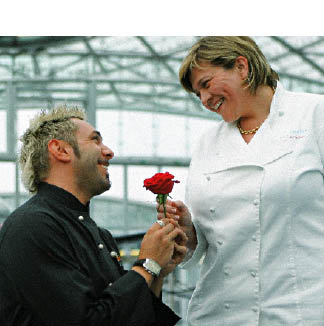 Ein Herr in einer schwarzen Kochjacke kniet vor einer Dame in weißer Kochjacke und schenkt ihr eine rote Rose