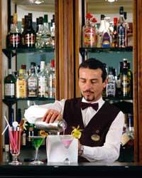 Ein Barkeeper steht hinter der Bar und mixt gerade einen Cocktail