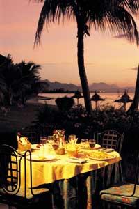 ein rosaroter Himmel, eine Palme und ein romantisch eingedeckter Tisch auf Mauritius