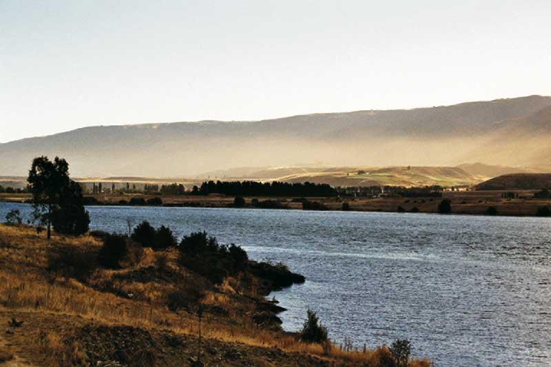 prachtvoll erstreckt sich die hügelige landschaft umschwebt von leichtem Nebellschwaden, in der mitte klares blaues wasser