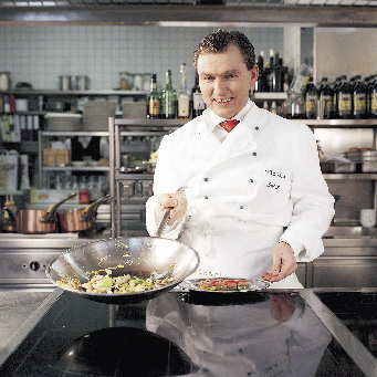 Toni Mörwald mit einer Pfanne in der Hand in der Küche