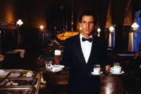 Ein Kellner im Anzug trägt diverse Heißgetränke und ein Bier