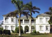 ein weißes Haus im Kolonialstil hinter zwei Palmen
