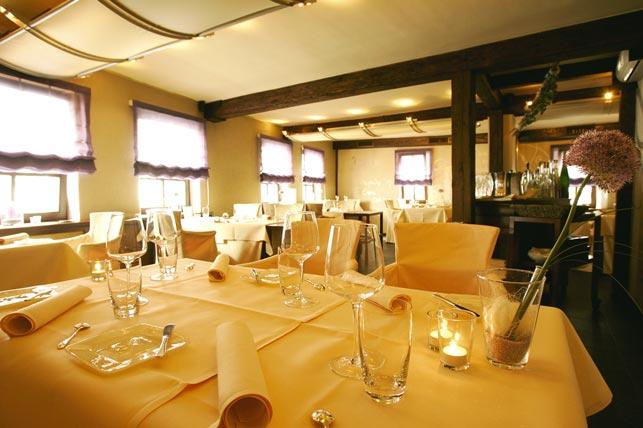 mehrere gedeckte Tische, überwiegend in Gelb gehalten in einem Restaurant sind zu sehen