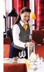 eine Mitarbeiterin bereit die Tische des Hotelrestaurant fuer das Dinner vor