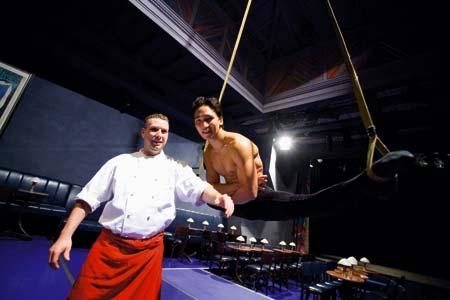 ein Koch und ein Akrobat in einem Spagat  posieren gemeinsam für ein Bild