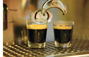 zwei Espressos werden aus der Kaffeemaschine heruntergelassen