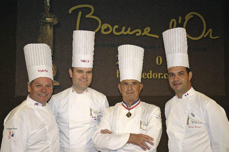 Paul Bocuse und Köche in Kochbekleidung posieren vor dem Logo des Bocuse d`Or