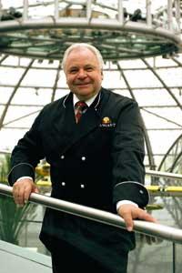Eckart Witzigmann steht an einem silbernen Geländer gelehnt da, in Kochuniform und sieht direkt in die Kamera