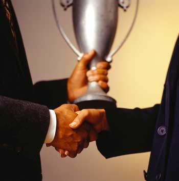 ein Handschlag zweier Männer ist zu sehen, während einer von ihnen einen Pokal in der anderen Hand hält